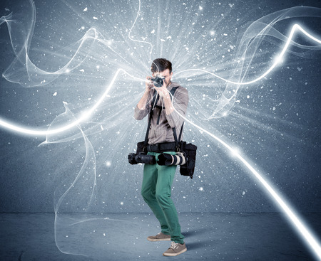 A young amateur photographer with professional photographic equipment taking picture in front of blue wall with dynamic white lines illustration concept Stockfoto