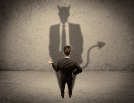 cuernos: Un hombre de negocios complicado con experiencia en el juego que mira a su sombra diablo desguise refleja en el concepto de la pared Foto de archivo