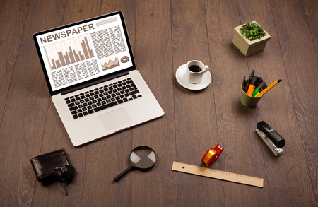 news values: Business laptop with stock market report on wooden desk and accessories