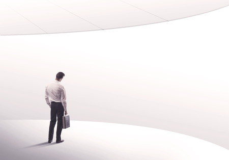 sales person: Young sales business person in elegant suit standing with his back in empty white space background with curved lines concept