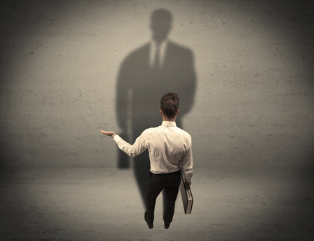 front facing: A young beginner salesman standing in front of a wall, facing his shadow as his boss or a successful businessman he lloks up to concept Stock Photo