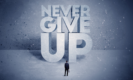 out of business: A stressed out business worker standing in front of huge block letters saying never give up in blue open environment concept