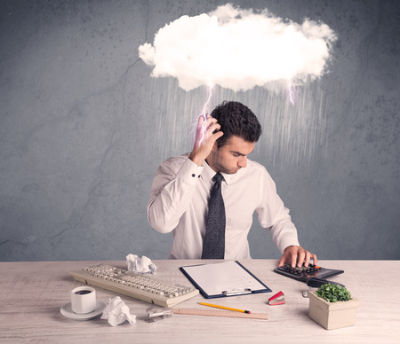 stressed man: An elegant office worker is having a bad day while working, illustrated by a white cloud above his head with heavy rain and thunder concept Stock Photo