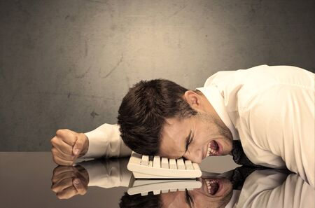 banging: A sad and depressed office worker resting his head on a keyboard while shouting in front of a grey grungy wall background
