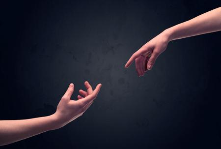 mano de dios: Dos hombres manos llegar a unos de otros, casi tocándose, frente a la pared de fondo concepto claro vacío oscuro