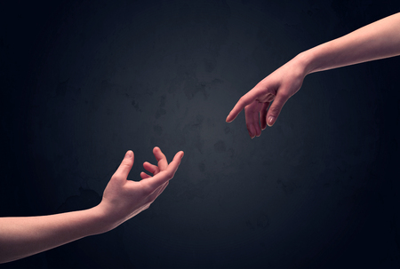 the human hand: Two male hands reaching out to one another, almost touching, in front of dark clear empty background wall concept