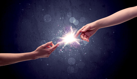 reaching: Two male hands reaching towards each other, almost touching with fingers, lighting spark in galaxy background concept