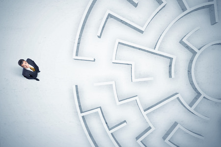 nowhere: Stressful business man looking at circular maze with nowhere to go