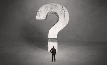 Eine kleine elegante Geschäftsmann im Anzug mit dem Rücken vor einem großen Fragezeichen in Freiraumkonzept stehen Standard-Bild - 49618355