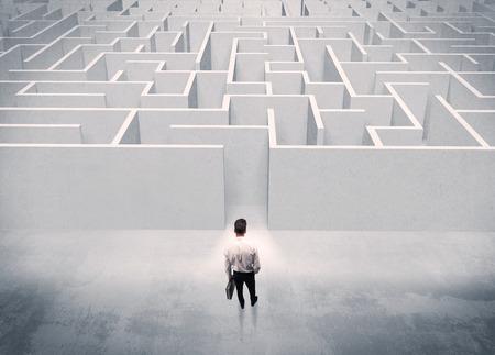 Een knappe zaken man met werkmap staan voor witte labirynth ingang op het punt om een beslissing begrip te maken