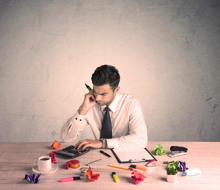bad planning: A young office worker sitting at desk working with keyboard, papers, highliter in front of empty clear background wall concept Stock Photo