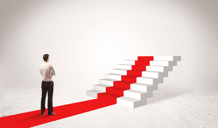 forward: A successful businessman with briefcase standing on red carpet in front of steps in white space concept