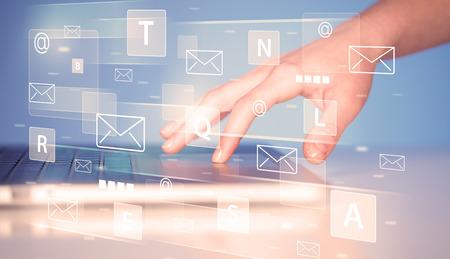 correo electronico: Mano que pulsa en el teclado con iconos y símbolos tecnología digitales