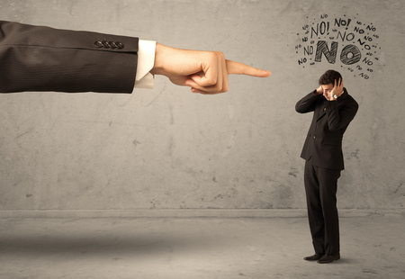 ashamed: A young employee disagreeing and arguing with boss, feeling ashamed concept. A large hand pointing at businessman saying no