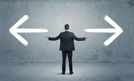 Un homme d'affaires dans le doute, avoir à shoose entre deux choix différents indiqués par des flèches pointant dans la direction opposée notion