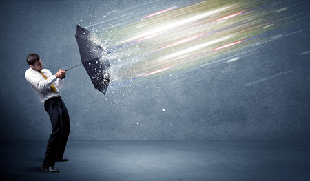 light beams: Business man defending light beams with umbrella concept on background