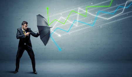Business person with umbrella and colorful stock market arrows concept Фото со стока