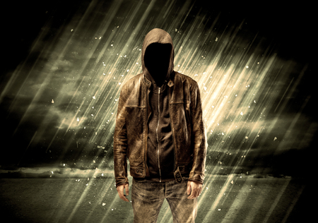 undercover: An incognito hooded stalker standing in the rain with his back in front of dark scary landscape concept