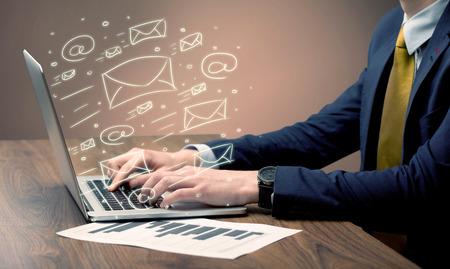 correo electronico: Un env�o de correos electr�nicos y de comunicaci�n con los clientes con la ayuda de un ordenador port�til port�til en concepto de servicio de empleado de oficina