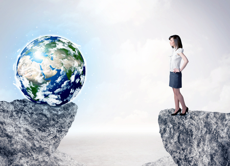 to the other side: Businesswoman standing on the edge of mountain with a globe on the other side Stock Photo