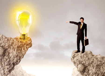 bridging the gaps: Businessman standing on the edge of mountain with an idea bulb on the other side