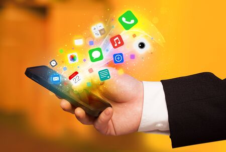 smartphone in hand: Hand holding smartphone with colorful app icons concept Stock Photo