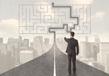 Biznesmen patrząc na drodze z labiryntu i koncepcji rozwiązania