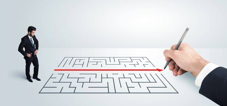 Business man looking at hand drawing solution for maze solution concept