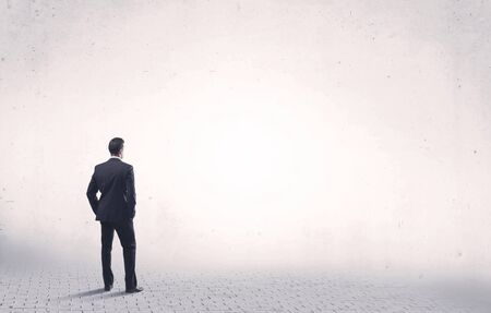 business men: Serious business man standing on grey brick floor and thinging about decisions concept