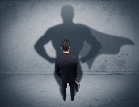 A confident young elegant salesman with briefcase facing a wall, looking at his superman shadow concept Standard-Bild