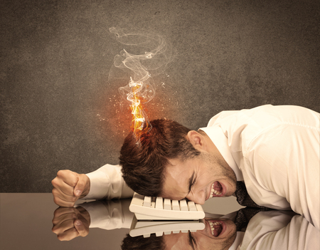 banging: A frustrated businessman resting his head on a keyboard and shouting with his hair on smoke, catching fire