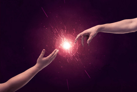 two generation family: White caucasian male hands reaching out with fingers almost touching in bright red light sparkle in empty space background concept