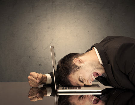 fed up: A sad and depressed office worker resting his head on a keyboard while shouting in front of a grey grungy wall background