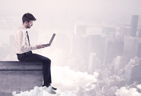 over the edge: An elegant young businessman sitting on the edge looking over urban city landscape with clouds concept
