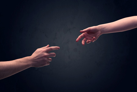 clear out: Two male hands reaching out to one another, almost touching, in front of dark clear empty background wall concept