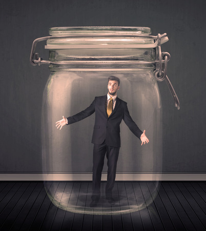 are trapped: Businessman trapped into a glass jar concept on background