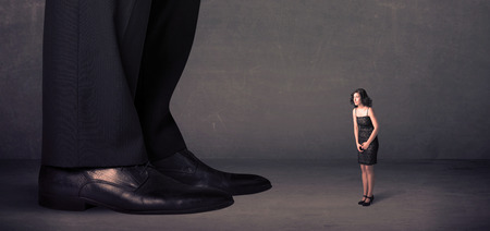 Huge legs with small businesswoman standing in front concept on background Stock Photo