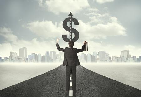 signos de pesos: Hombre de negocios en carretera en dirección hacia un concepto de signo de dólar Foto de archivo