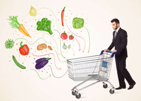 Businessman pushing a shopping cart and healthy vegetables coming out of it Stock Photo