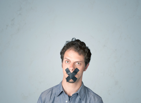 Hombre joven con la boca pegada. Aislado en el fondo gris