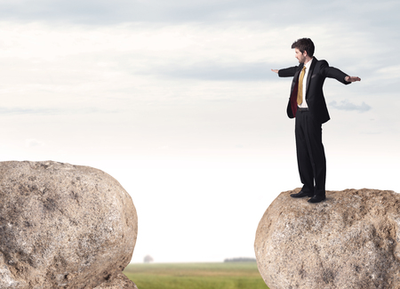 bridging the gaps: Young businessman standing on edge of rock mountain