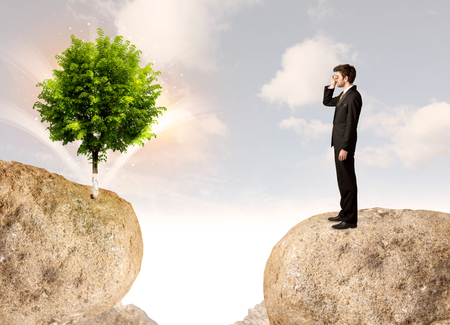 bridging the gap: Businessman standing on the edge of rock mountain with a tree on the other side Stock Photo
