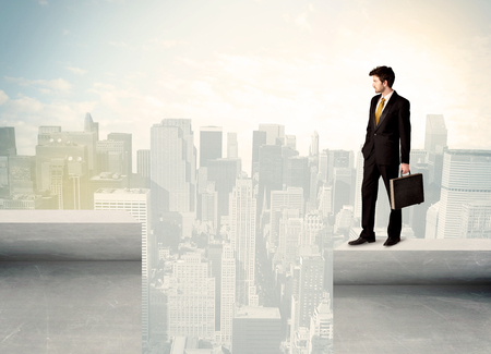 bridging the gaps: Businessman standing on the edge of rooftop with city background Stock Photo