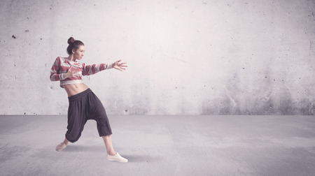 DAnce background: A beautiful young hip hop dancer dancing contemporary urban street dance in empty clear grey wall background concept.
