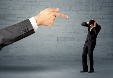 you are fired: Boss firing employee concept with a huge hand pointing at confused business person illustrated by drawn lines in front of grey brick wall