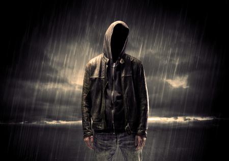 ladron: Un ladrón sin rostro irreconocible en hoodie de pie en medio de la noche bajo la lluvia frente a concepto de paisaje Foto de archivo
