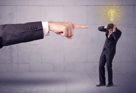 you are fired: A huge ordering hand pointing at scared and confused businessman with a good idea illustrated by a drawn glowing light bulb concept Stock Photo