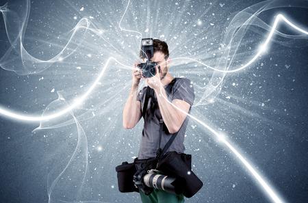 AFICIONADOS: Un joven fotógrafo aficionado con equipos de fotografía profesional que toma el cuadro en frente de la pared azul con líneas blancas dinámico concepto de ilustración