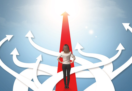 strategic: Concept of confused businesswoman with different direction arrows Stock Photo