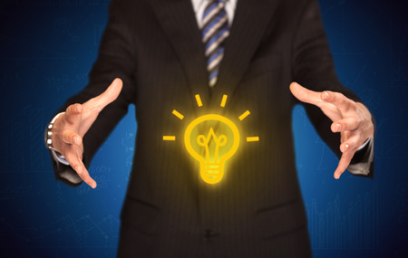 idea symbol: A creative businessman has a great bright idea illustrated by holding a drawn light bulb in the hand concept Stock Photo